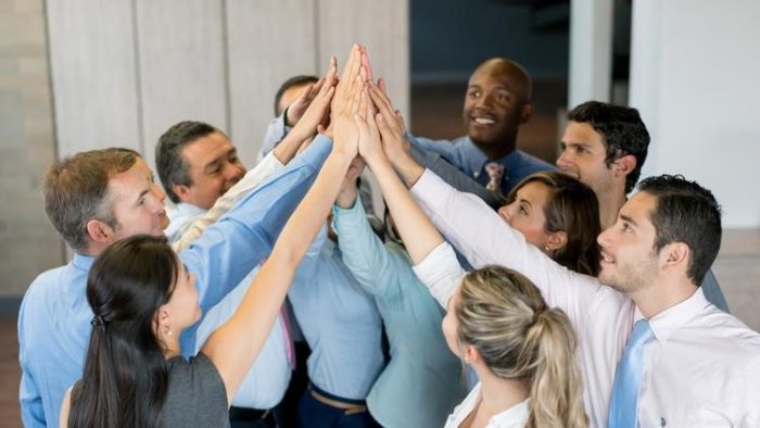 Office team coming together for a group high five